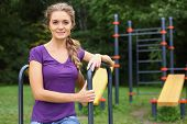 Beautiful smiling girl with a plait on the outdoor sports ground
