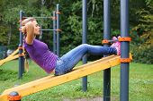 picture of crunch  - A young girl doing abdominal crunches on the outdoor sports ground - JPG