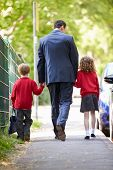 Father Walking To School With Children On Way To Work