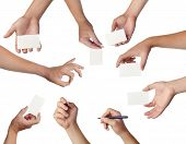 Set of hands holding empty business cards on white