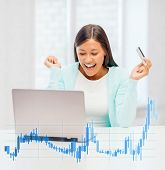 banking, business, office and money concept - smiling businesswoman with laptop, credit card and forex chart