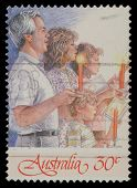 AUSTRALIA - CIRCA 1988: A Christmas stamp printed in Australia shows family singing with candles, circa 1988