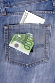 One Hundred Euro Note In The Back Pocket Of Jeans Full Of Holes. The Concept Of Poverty, Wastefulnes