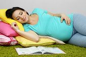 Young pregnant woman lying on floor and sleeping on wall background
