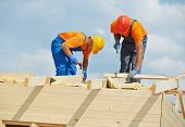 stock photo of reconstruction  - Two construction carpenters roofers workers installing wood board roof - JPG