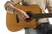 stock photo of guitarists  - Guitarist strumming the strings playing an acoustic guitar - JPG
