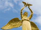 stock photo of angel-trumpet  - Sculpture of golden angel with pigeon in hands - JPG