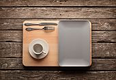 Empty ceramic dish with empty coffee cup and knife and fork on old wooden table.
