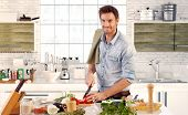 pic of single man  - Happy handsome man cooking in kitchen at home - JPG