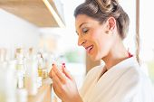 Woman in bath robe choosing face care products in wellness spa
