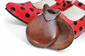 spanish castanets and typical dot-patterned red flamenco shoes, on a white background