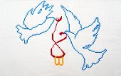 Embroidered good by cross-stitch pattern. White doves holding wedding rings