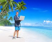 Businessman holding a laptop on a beach.
