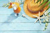 Summer holiday setting with straw hat and cocktail