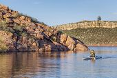 senior male paddling a decked expedition canoe on Horsetooth Reservoir near Fort Collins, Colorado