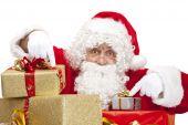 Santa Claus hinter Weihnachten Geschenk-Boxen ist mit seinen Fingern auf sie verweist.