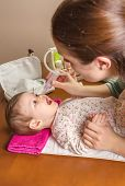 foto of nasal catarrh  - Mother cleaning mucus catarrh of adorable baby with a nasal aspirator - JPG