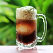 stock photo of floating  - Root beer float a tasty summer treat on Green tree background - JPG