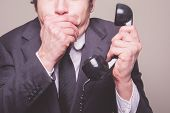 Businessman On Phone Covering His Mouth