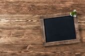 foto of dainty  - Old blank vintage school slate or chalkboard lying on an old rustic wooden background with dainty white flowers in two corners ready for your text or message - JPG