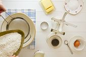 picture of devonshire  - Ingredients for English scones laid out on white wood with flour being sieved - JPG