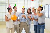 Casual business team celebrating with champagne and party poppers in the office