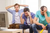 friendship, sports and entertainment concept - sad male friends with vuvuzela watching sports on tv