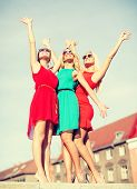 holidays and tourism, friends, hen party, blonde girls concept - three beautiful women in the city waving hands
