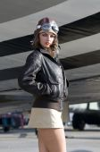 stock photo of bomber jacket  - female aviator dressed in a black bomber jacket standing in front of an aircraft - JPG