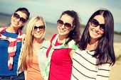 summer, holidays, vacation, happy people concept - beautiful teenage girls or young women having fun