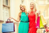 sale, tourism, shopping and happy people concept - two beautiful women with shopping bags in the cti