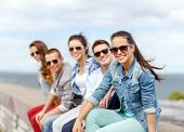summer holidays and teenage concept - smiling teenage girl in sunglasses hanging out with friends ou