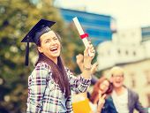 education, campus and teenage concept - smiling teenage girl in corner-cap with diploma and classmates on the back
