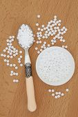Sugar sweetener tablets in a spoon, bowl and on a beech wood board.