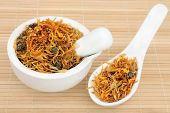 Dried calendula flowers used in chinese herbal medicine in a porcelain mortar with pestle and spoon.