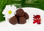 foto of truffle  - Arrangement of chocolate truffles with daisy and leafs - JPG