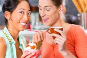 Young female customers or friends in an ice cream parlor with ice cream cornet