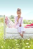stock photo of 7-year-old  - 7 years old child resting on comfortable bed in spring field - JPG