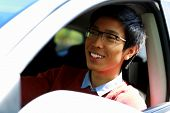 Handsome happy asian man sitting in car