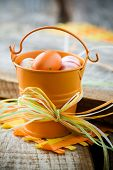 Colourful easter eggs in orange bucket, selective focus