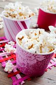 Pop corn in pink carton cups, selective focus