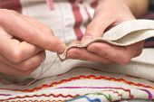 pic of thread-making  - Woman hands sewing with needle and thread [[** Note: Shallow depth of field] ** Note: Visible grain at 100%, best at smaller sizes - JPG