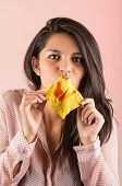stock photo of chinese crackers  - protrait of young brunette girl eating chinese wonton cracker snack over pink background - JPG
