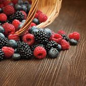 different berries (blueberries raspberries blackberries) in a basket on a wooden table
