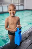 Little boy holding flippers by the pool at the leisure center
