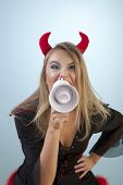 Girl in devil costume is getting mad and shouting from megaphone.