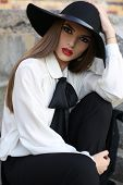 Portrait Of Beautiful Girl With Dark Hair In Elegant Blouse And Hat