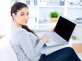 Woman using a laptop in the living room as she sits on a comfortable sofa turning to look at the camera with a smile