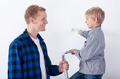 Father Learning His Son Painting A Wall