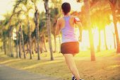 Runner athlete running at tropical park. woman fitness jogging workout wellness c